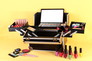 open case with cosmetics on yellow background