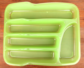 Green plastic cutlery tray on wooden table