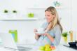 hübsche junge frau mit laptop in der küche