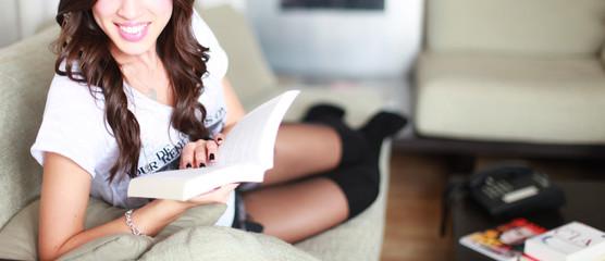 Junge Frau liegt auf dem Sofa und liest