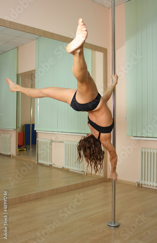 Girl pole dancing in the studio