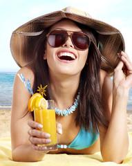 Girl in bikini on beach drinking cocktail.