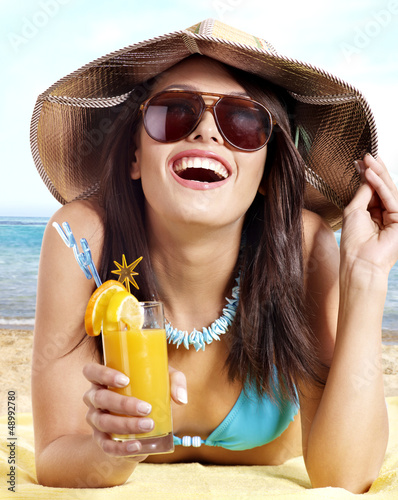 Girl in bikini on beach drinking cocktail.