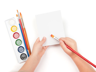 blank sheet in child hand with watercolor brush