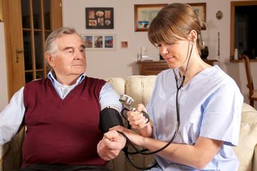 Krankenschwester misst Blutdruck bei Senior