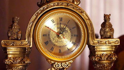 The arrows of the antique clock show 12:00.