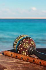 Музыкальные инструменты маракас и флейта на фон моря