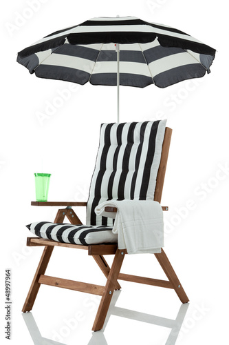 Beach chair with umbrella, towel and drink