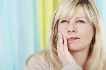 Frau mit Zahnschmerzen fasst an die Backe