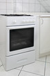 White gas cooker in white tiled kitchen