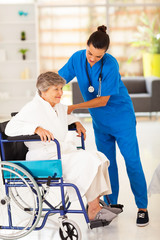 friendly caregiver helping senior woman on wheelchair