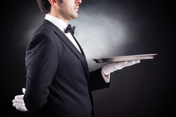 Cropped image of a young waiter holding an empty dish on black b