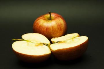 manzana partida por la mitad y otra al fondo