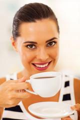 closeup of beautiful young woman drinking tea
