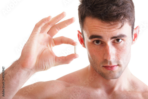 Closeup of handsome man holding pills
