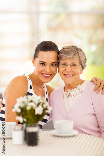 pretty young woman and grandmother having coffee together