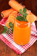 Glass of carrot juice on wooden table