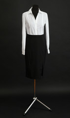 White blouse and black skirt on mannequin on black background