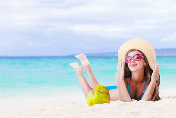 smiling young woman in straw hat with coconut on the beach
