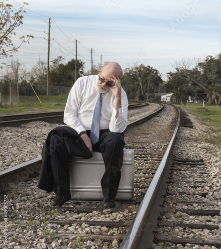 Jobless business man sits on suitcase on railroad tracks