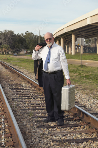 Jobless senior businessman on railroad tracks with suitcase