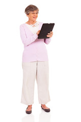 happy senior woman using tablet computer isolated on white