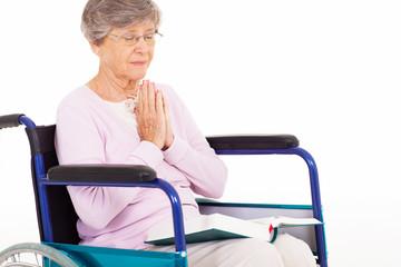 senior woman praying on wheelchair isolated on white