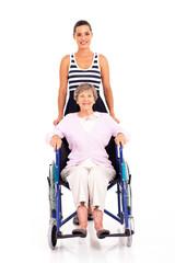 granddaughter pushing disabled senior grandmother on wheelchair