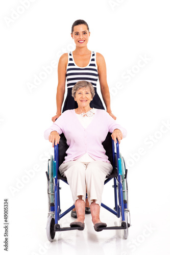 granddaughter pushing disabled senior grandmother on wheelchair