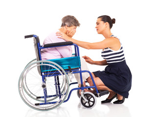 young woman comforting disabled senior mother on white