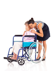 caregiver hugging and comforting lonely disabled senior woman