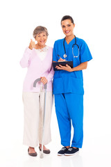 senior woman giving thumb up to medical service with nurse