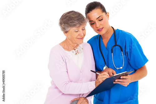 senior woman signing medical form with help from nurse