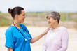 happy young nurse talking to senior woman outdoors