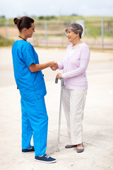 young nurse in uniform talking to senior woman outdoors