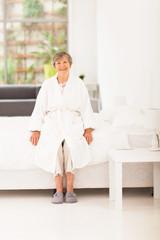 happy elderly woman in pajamas sitting on bed