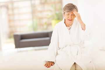 senior woman sitting on bed and having headache