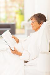 elegant senior woman lying on bed reading a book