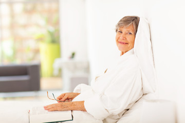 peaceful elderly woman reading book on bed