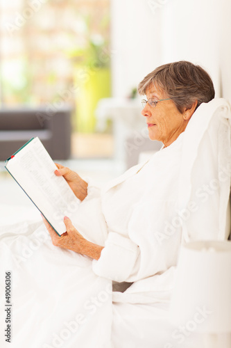 elegant senior woman lying on bed reading a book