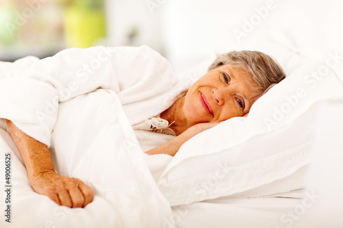 happy senior woman sleeping on bed