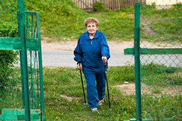 Active old woman nordic walking outdoors, 85 years old.