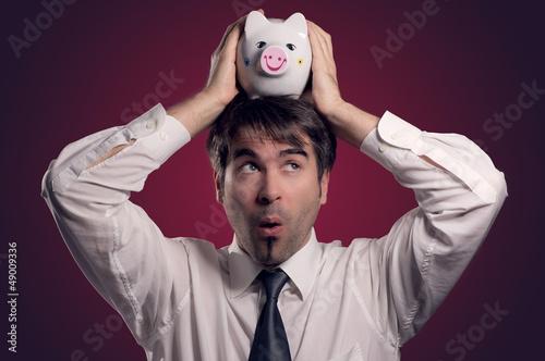 Mann mit Sparschwein auf dem Kopf