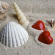 zwei rote Herzen im Sand