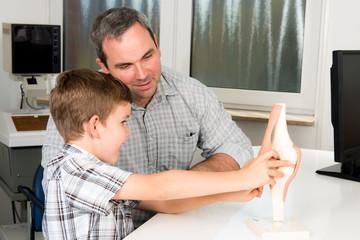 orthopäde erklärt einem kind das kniegelenk