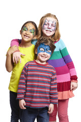 Young boy and two girls with face painting of cat butterfly and