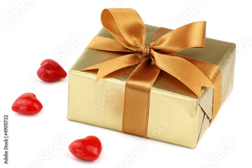 Valentine day's gift wrapped in golden paper with bow and hearts