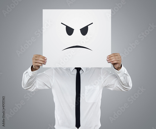 Young businessman holding card with a angry face on it