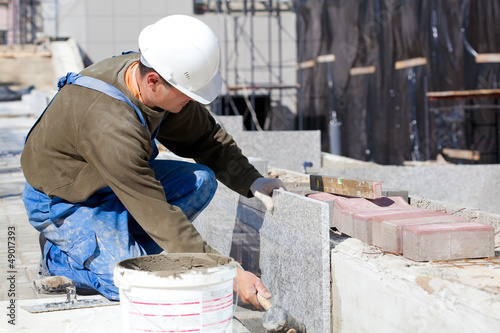 Tiler in helmet and work wear installing marble tiles