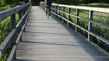senior old man with cap drive bicycle wooden long bridge lake